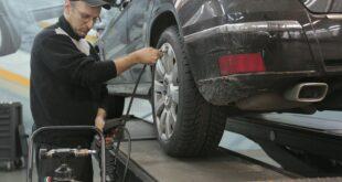 Un homme change un pneu dans un centre de montage agréé. L'importance de changer les pneus.