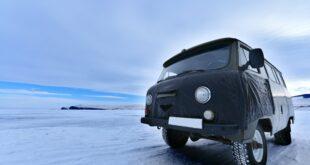Pneu hiver ou été ? Une camionnette noire est sur une route enneigée
