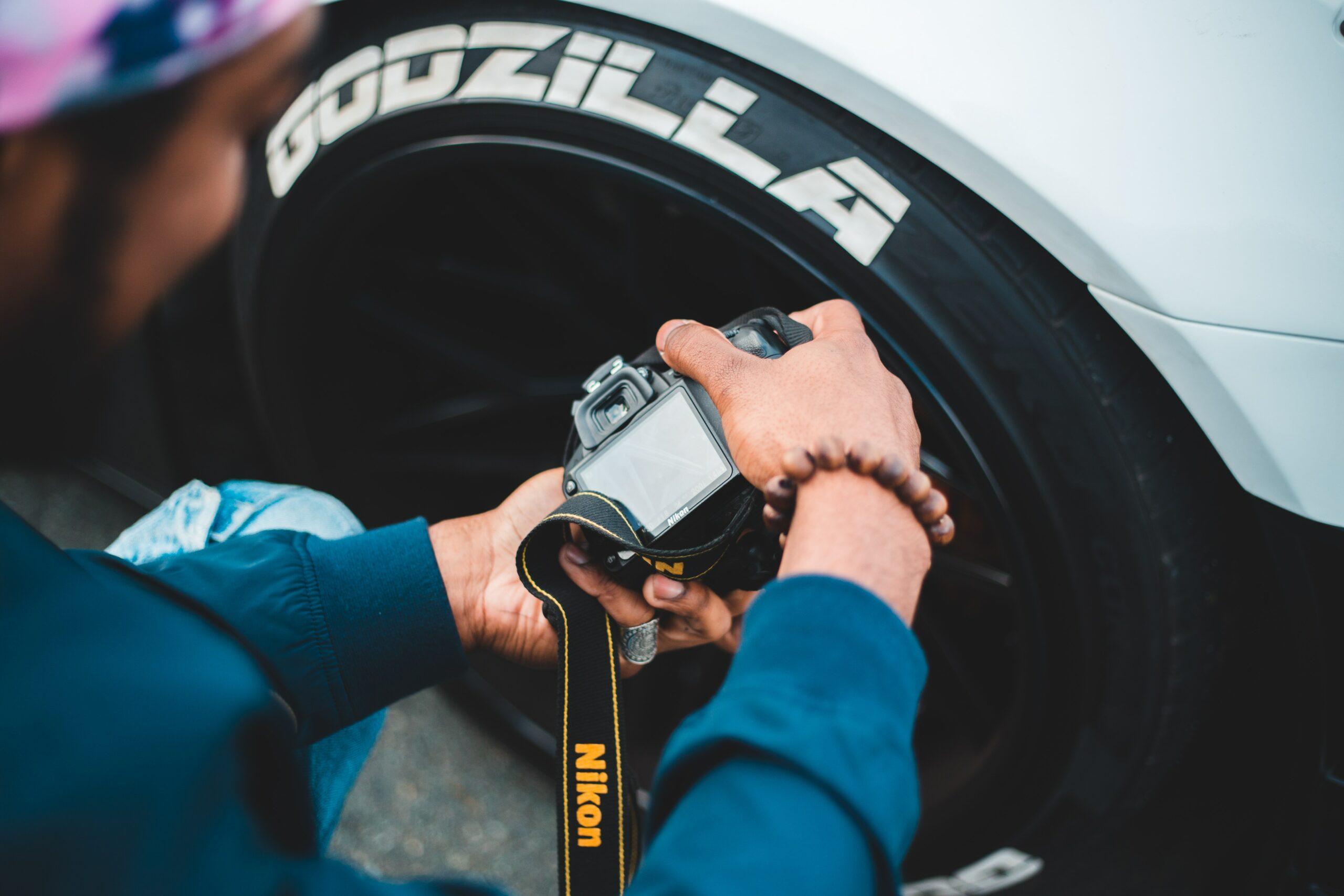 Un homme photographie un pneu monté Godzilla. Contrôler l'usure des pneus est fondamental.