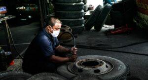 Comment est fabriqué un pneu ? Usine de fabrication de ce type de produits. Un homme finit un pneu