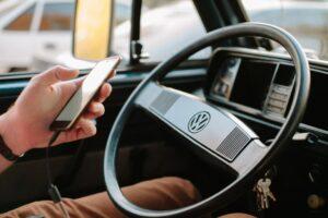 Utilisation du téléphone portable en voiture. Un utilisateur d'une voiture conventionnelle utilise son portable lors de la conduite.