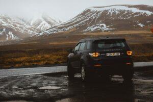 Quel type de pneu choisir ? Véhicule noir garé dans une montagne. Le paysage est neigé.