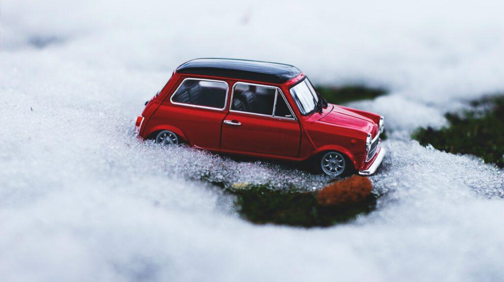 Chaîne neige. Une petite voiture rouge posée sur la neige.